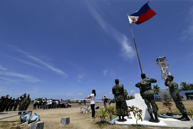 PHILIPPINE FLAG. Filipino residents and soldiers conduct a flag raising ceremony during the visit of Armed Forces of the Philippines military chief General Gregorio Catapang Jr in Pag-asa (Thitu) island on May 11. Photo by Ritchie Tongo/EPA