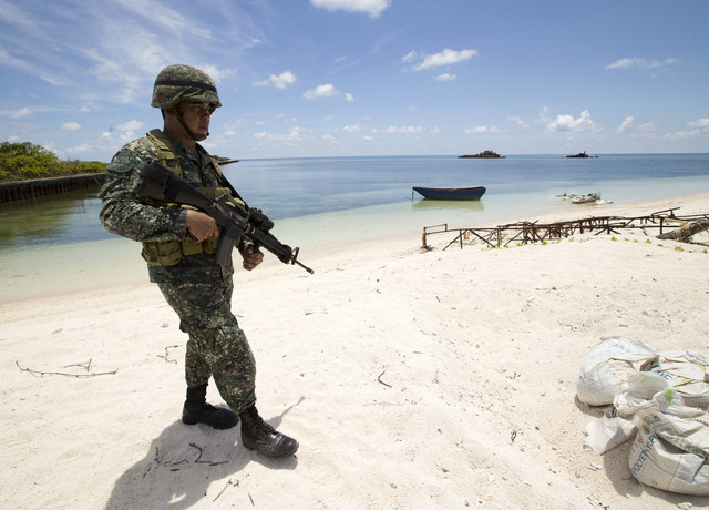 MARINE. Filipino soldier Tychico Octobre patrols on the shores of Pagasa (Thitu) island  in the Spratlys. Photo by Ritchie Tongo/EPA