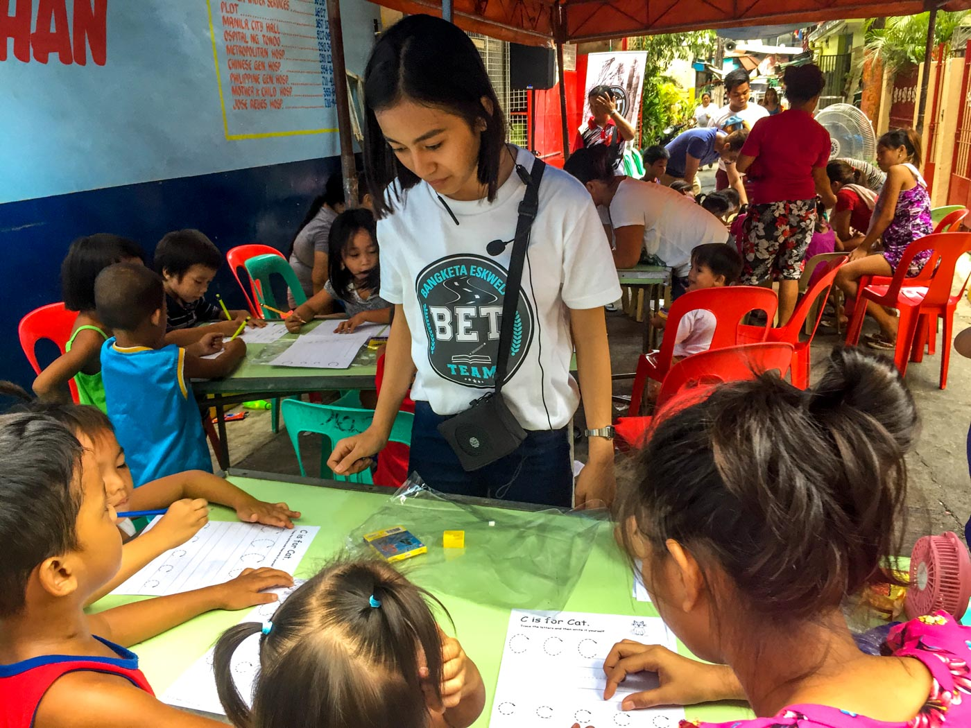 THE TUTOR. Dara Mae Tuazon oversees the students' worksheets and gives them words of encouragement to do their best. Photo by Luisa Jocson