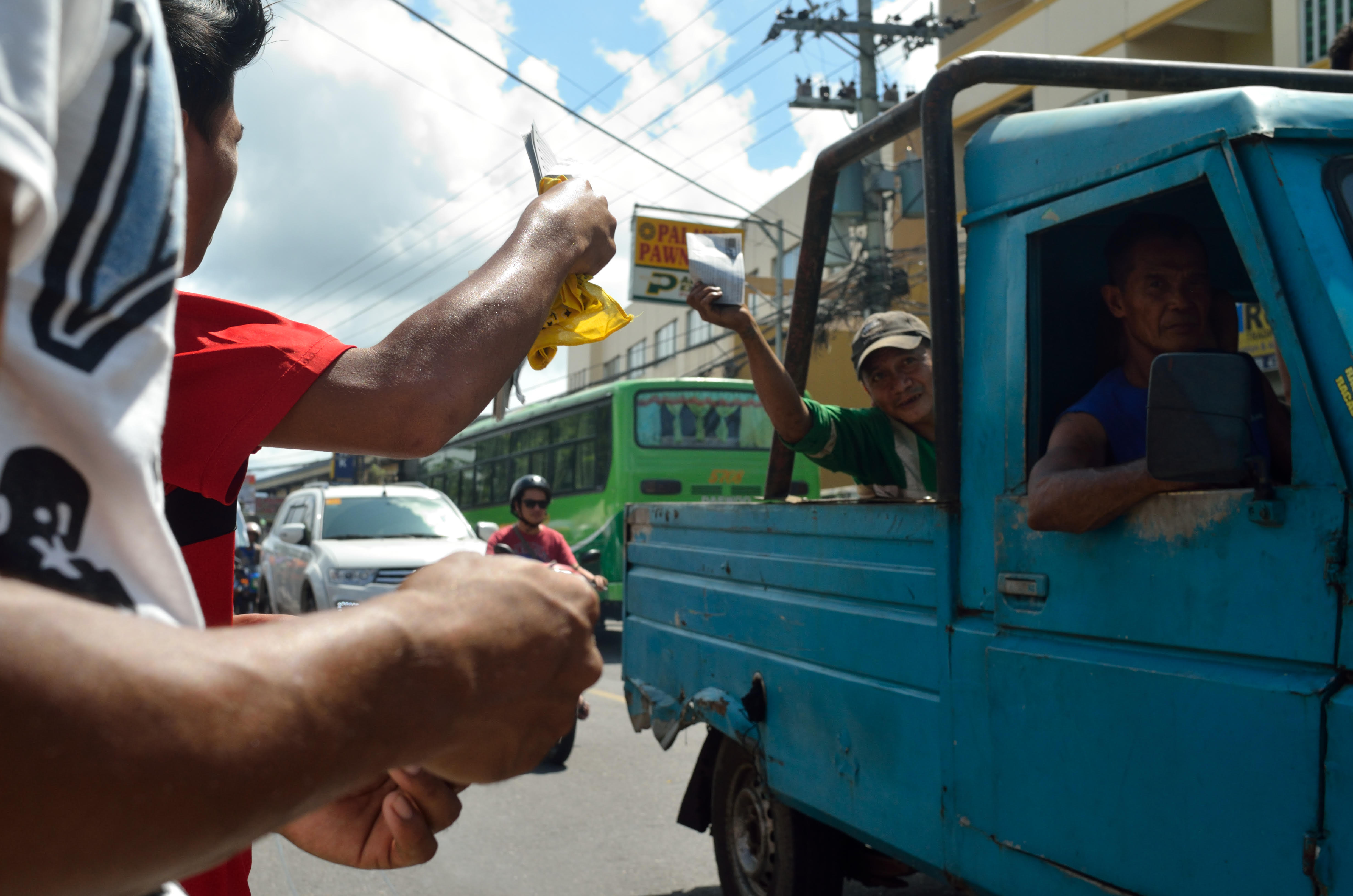 NAGA. Protesters give out pamphlets to passing vehicles. Photo by Miguel Imperial/Rappler