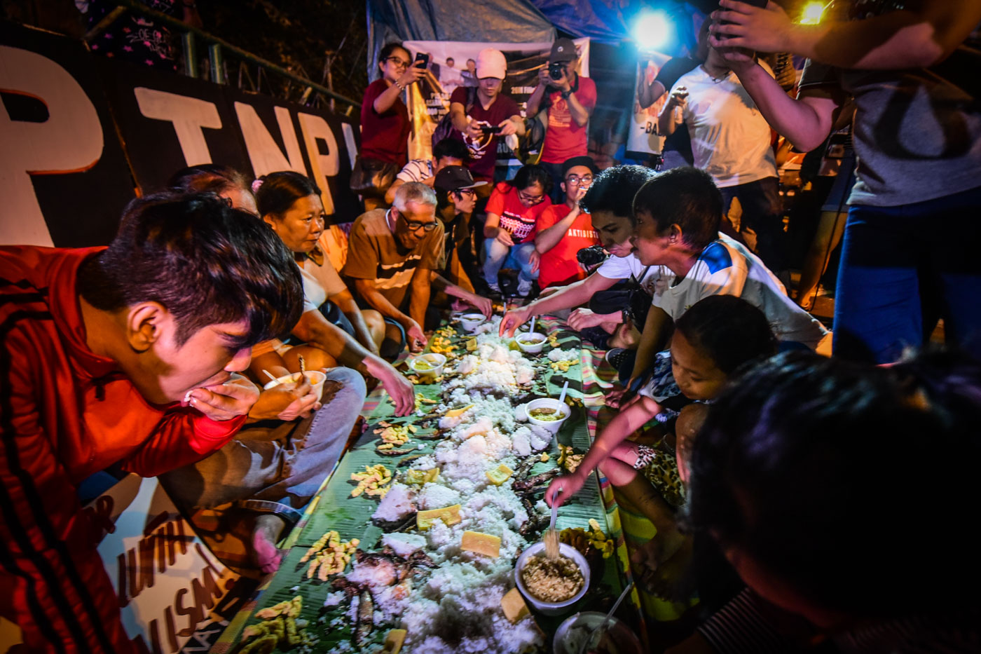 BOODLE FIGHT. Protesters throw a boodle fight to juxtapose the supposed dinner of the 'ruling elite' and that of the 'ordinary Filipino masses.' Photo by Alecs Ongcal/Rappler