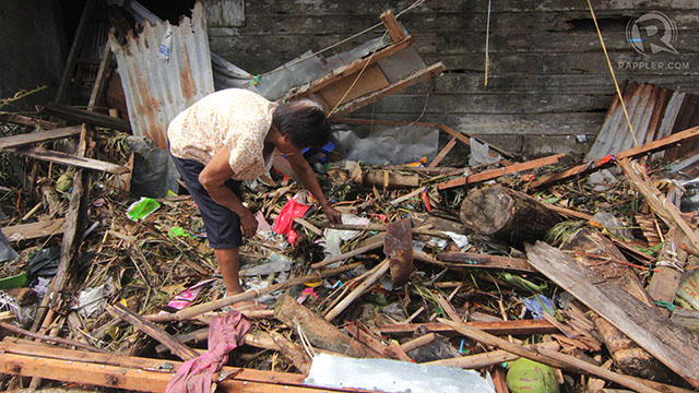 AFTERMATH. A woman picks up what's left of her belongings in the rubble after the floodwaters subsided in Eastern Samar. File photo by Franz Lopez/Rappler