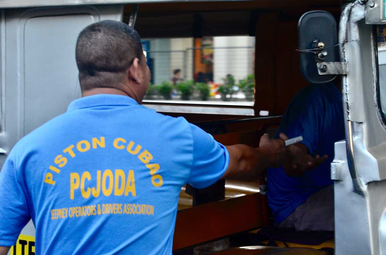 A member of Piston gives handouts to fellow jeepney drivers. Photo by Angie de Silva/Rappler