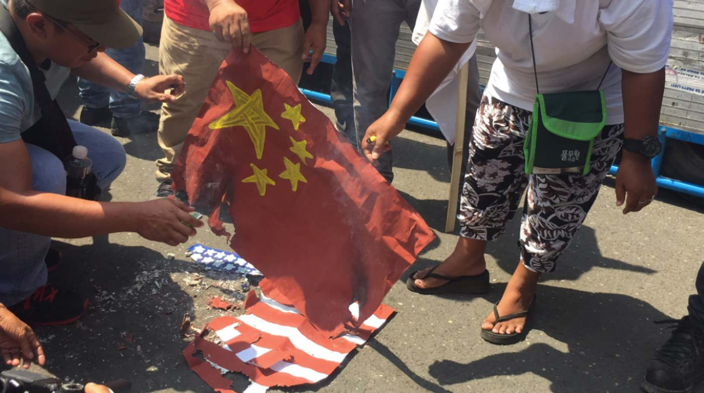 CEBU. Progressive groups burn the flags of the United States and China in front of Metro Colon in Cebu City during the Independence Day protest on Wednesday, June 12. Photo by Micole Gerard Tizon/Rappler