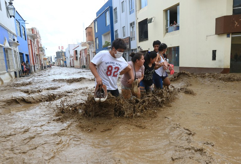 PERU CALAMITY. Residents wade through the water as a flash flood hits the city of Trujillo on March 18, 2017, bringing mud and debris. Photo by Celso Roldan/AFP