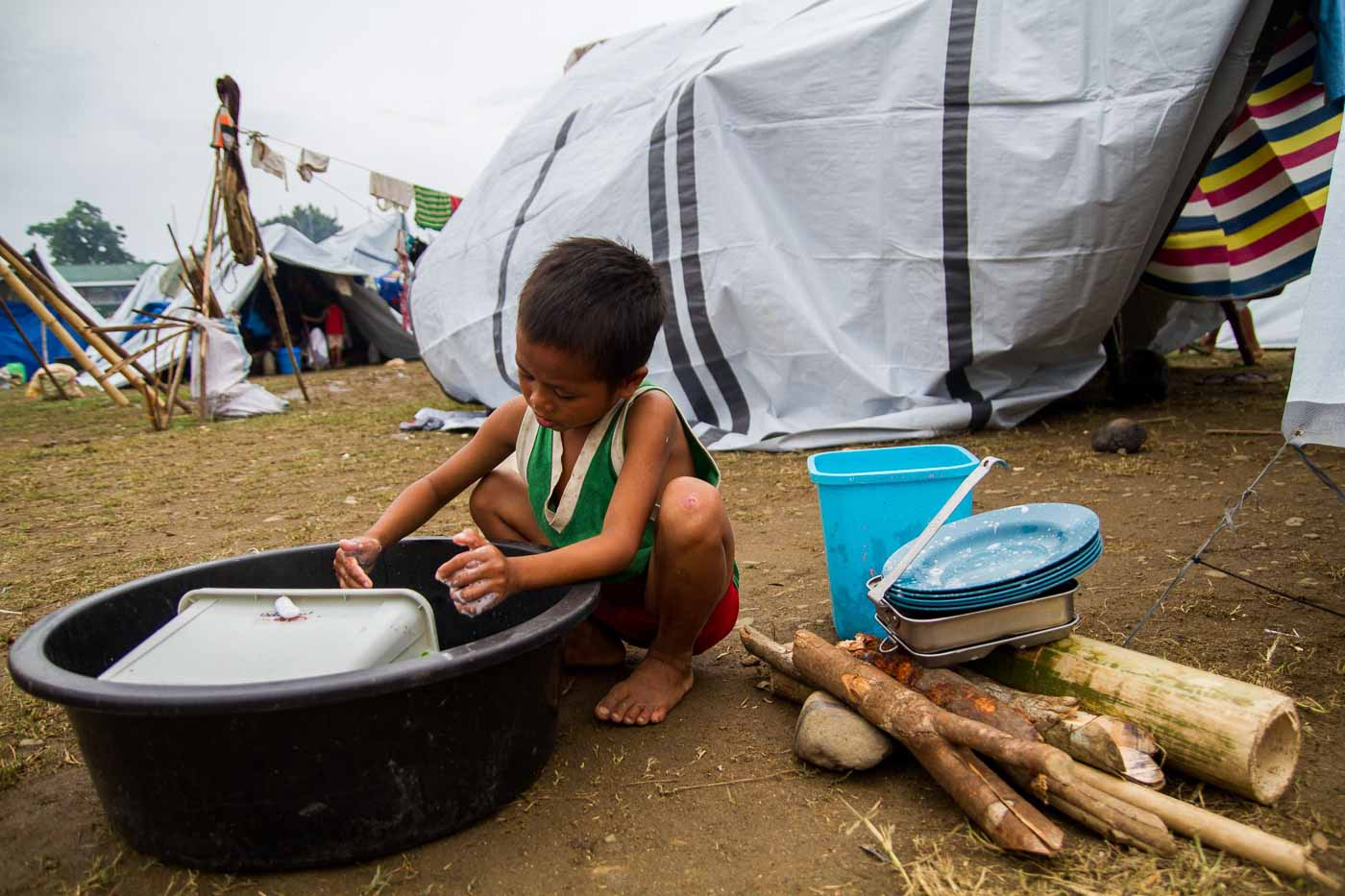 CAUGHT IN THE CROSSFIRE. A Lumad child washes dishes after the family's meal.
