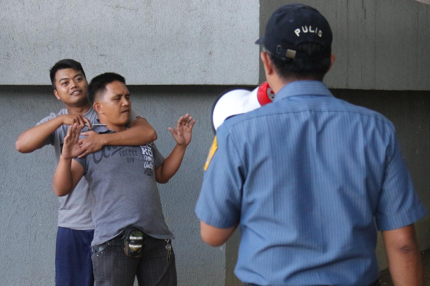 'HOSTAGE'. A cop pretends to negotiate during a mock hostage-taking in Pasig City during the #MMShakeDrill. Photo by Darren Langit/Rappler