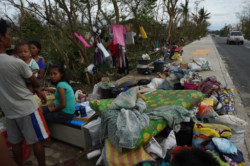 HARD ROAD AHEAD. A family gathers their belongings along a highway after their house was destroyed by super typhoon Haima, in San Pablo town, Isabela province, north of Manila on October 20, 2016. Photo credits: Ted Aljibe/AFP