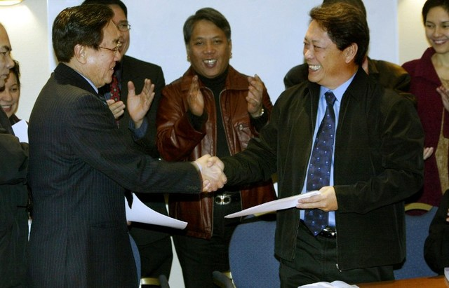 RESUMPTION. Goverment chief negotiator Silvestre Bello III (R) and the head of the Communist rebel delegation Luis Jalandoni shake hands February 14, 2004 after signing a joint statement, putting the peace process back on track, more than two years after the first talks collapsed. AFP photo