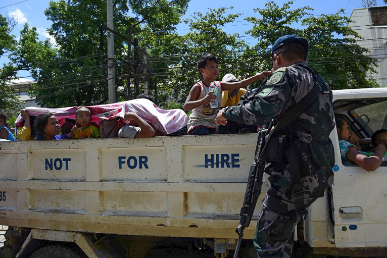 Policemen check a car boot of a resident fleeing from Marawi city, where gunmen who had declared allegiance to the Islamic State group rampaged through the city, at a checkpoint in Iligan City on May 24, 2017. Photo by Ted Aljibe/AFP