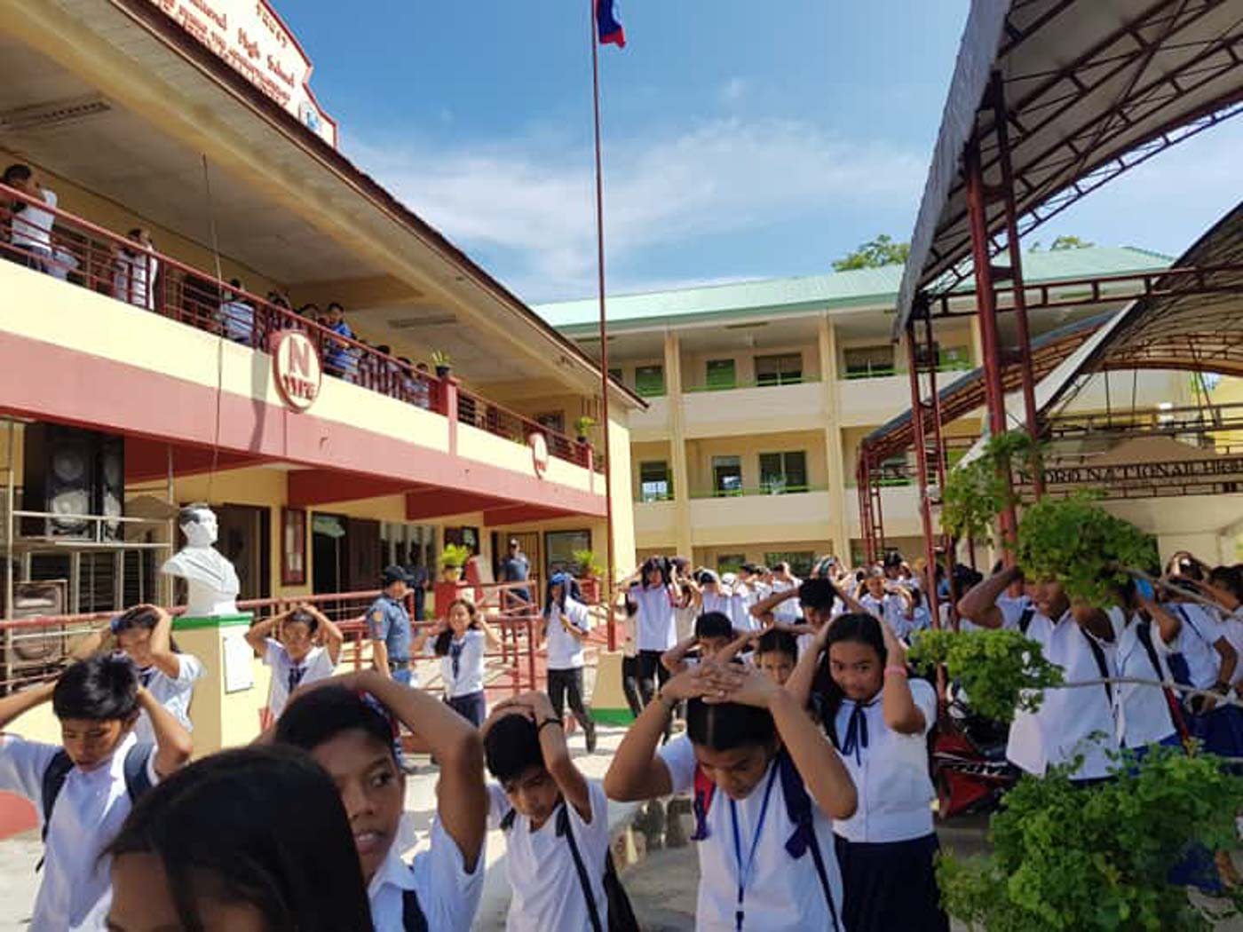 ASSIST. Students and staff of the San Isidro National High School are assisted by members of the local police. Photo from Catanauan Police Facebook page