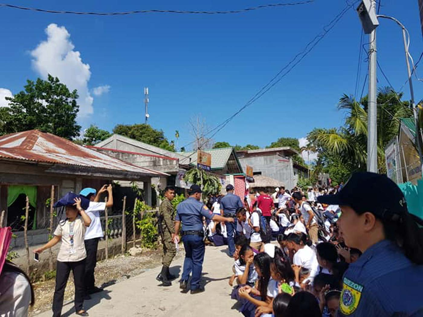 LEAD. Police officers help lead the conduct of the nationwide earthquake drill for students and staff of the San Isidro National High School. Photo from Catanauan Police Facebook page