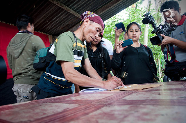 RELEASE PAPERS. Ka Dindo, head of the sub-regional committee of the Far South Mindanao Region-NPA command, signs Subere's release papers.