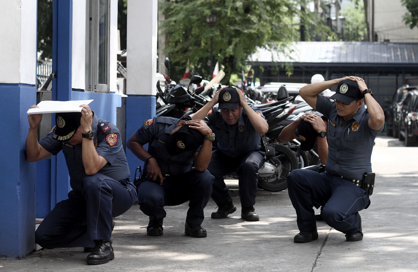 DUCK. Policemen at the Manila Police District headquarters take cover during the earthquake drill on June 29, 2017. Photo by Inoue Jaena/Rappler