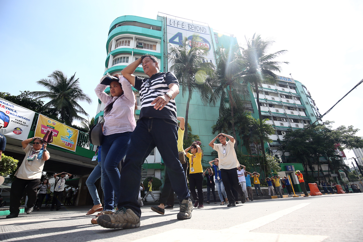 STAFF. MMDA employees cover their heads as they go out of the office. Photo by Ben Nabong/Rappler