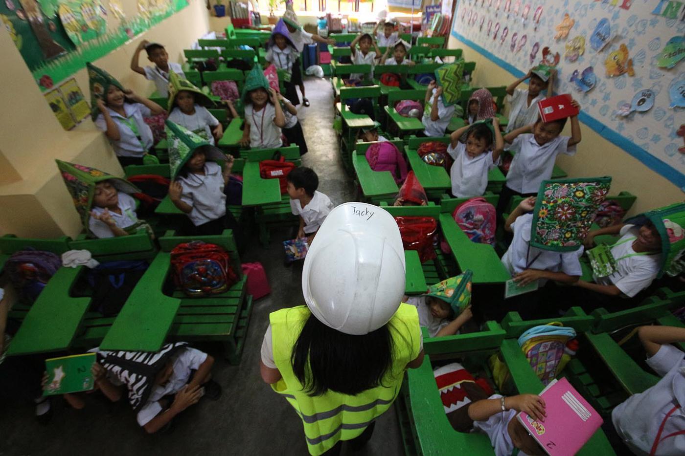 PRACTICE. Students of Corazon C. Aquino Elementary School in Batasan, Quezon City, cover their heads. Photo by Darren Langit/Rappler