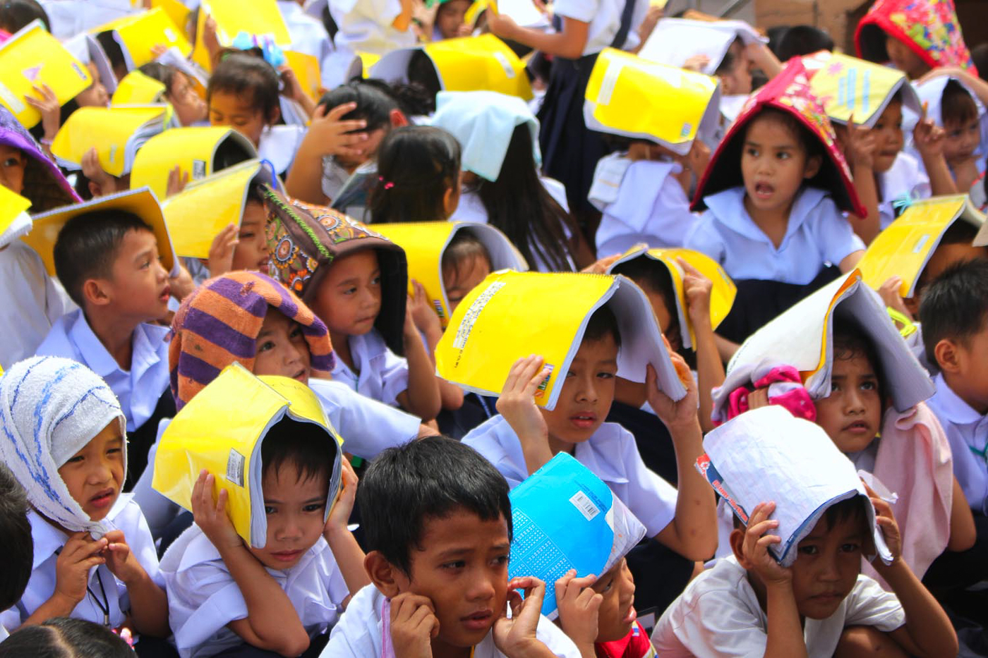 COVER. Students cover their heads with notebooks during the earthquake drill. Photo by Darren Langit/Rappler