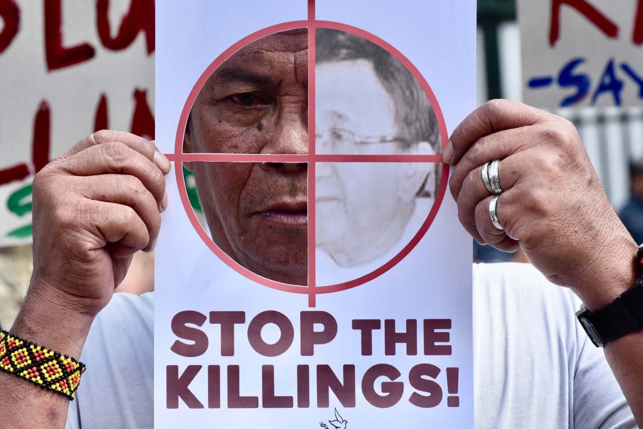 STOP THE KILLINGS. A protester holds a placard that shows half of his face in Camp Aguinaldo in Quezon City. All photos by Angie de Silva/Rappler