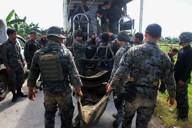 SLAIN COMRADES. Philippine police commandos load body bags containing the remains of their comrades killed in a clash with Muslim rebels onto a truck in Mamasapano, Maguindanao, on January 26, 2015. Photo by Mark Navales/AFP