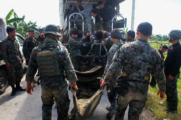 RETURN WEAPONS. Philippine police commandos load a truck with body bags bearing the remains of comrades killed in a clash with Muslim rebels in Mamasapano town, in Maguindanao on January 26, 2015. File photo by Mark Navales/AFP