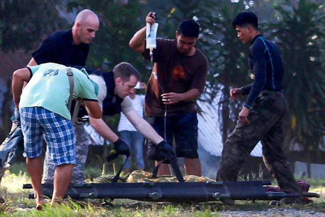 US military personnel (L) help their Philippine counterparts prepare to load an injured police commando from one stretcher to another and onto a waiting US military helicopter in the town of Mamasapano on January 26, 2015, following clashes with Muslim rebels. File photo by Mark Navales/AFP