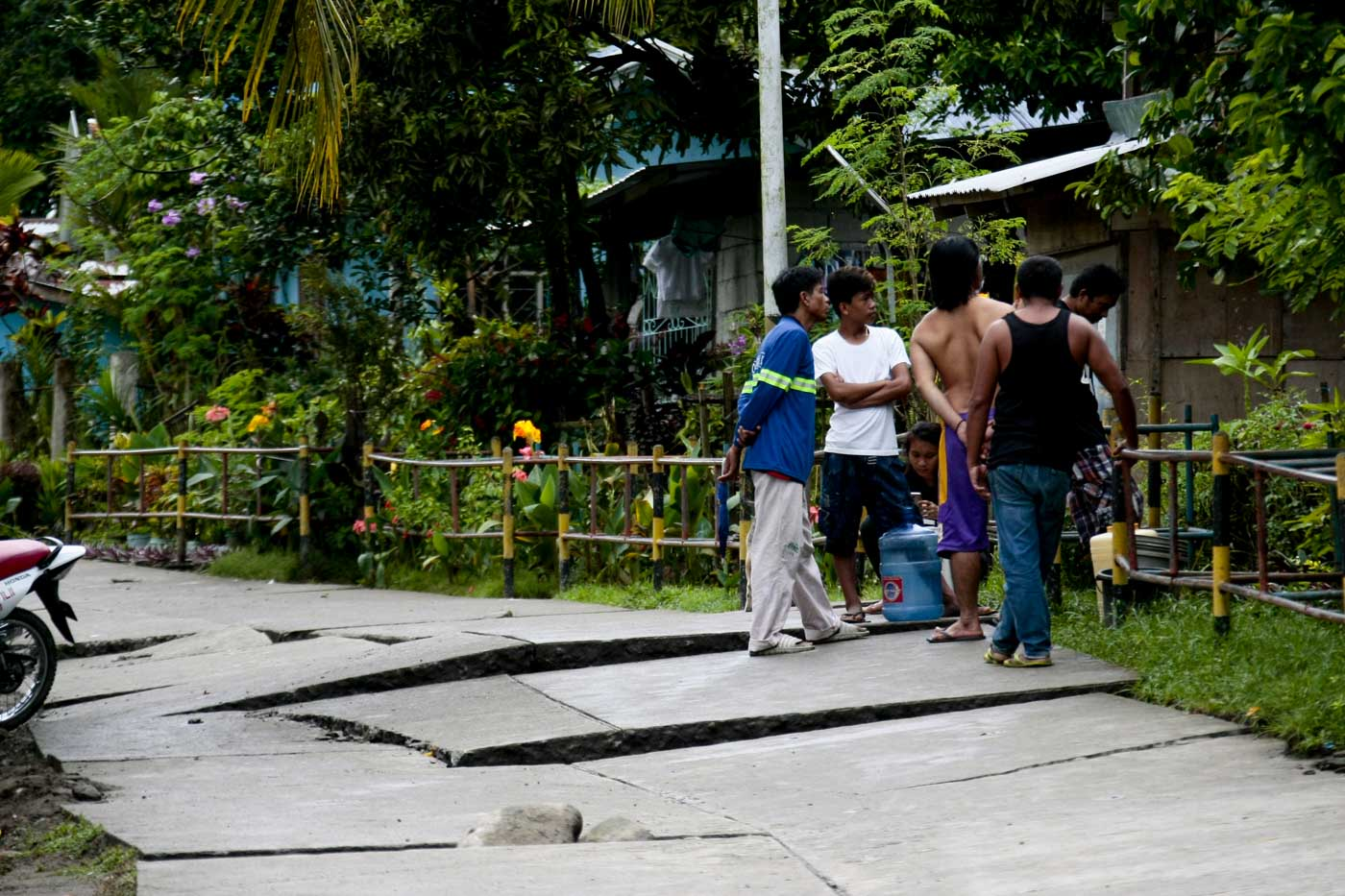 WAITING FOR REPAIRS. Residents gather by a road damaged by the quake. Photo by Gelo Litonjua