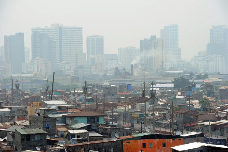 WHOSE CITY? This general view shows informal settlers' homes dwarfed by high-rise buildings near the port of Manila on August 20, 2014. File photo by Ted Aljibe/AFP