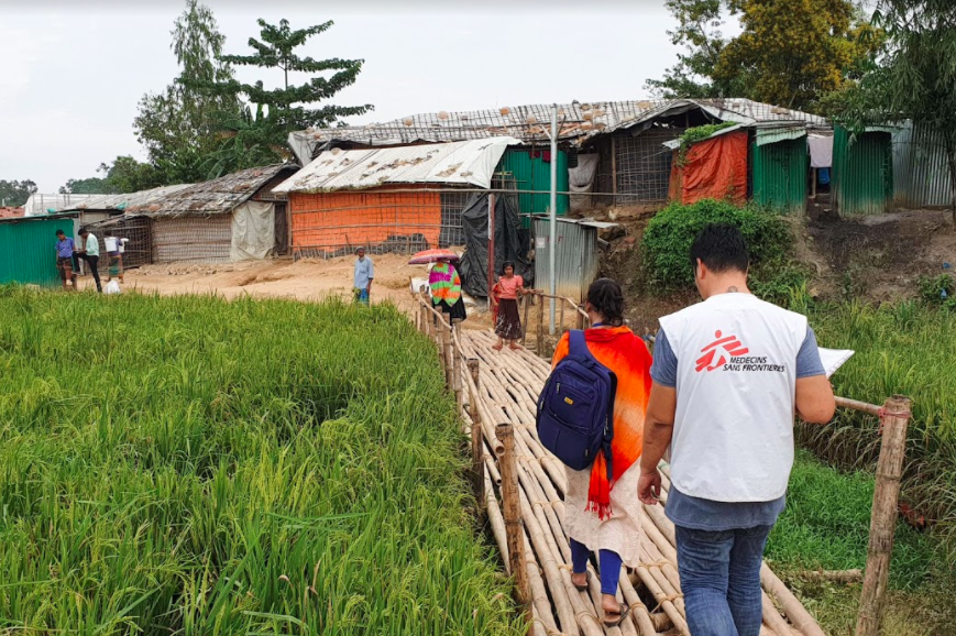 THE BRIDGE. Healthcare workers from Médecins Sans Frontières walk along a bamboo bridge to get to the refugee community. All photos courtesy of Médecins Sans Frontières