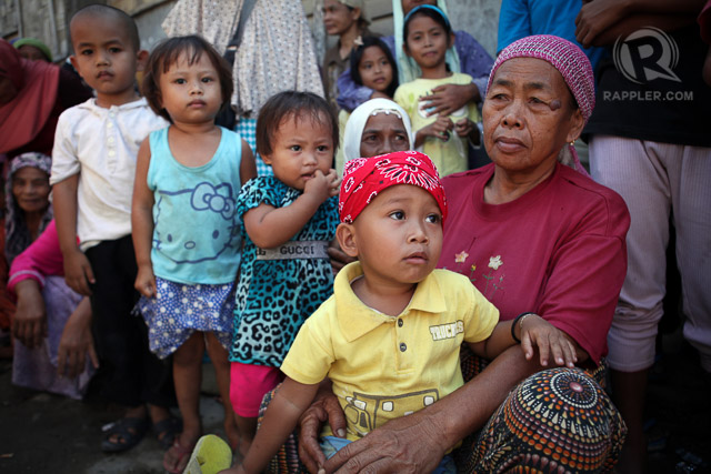 ANOTHER CLASH: Children affected by the conflict in the village of Tukanalipao, Mamasapano, Maguindanao are seen with their parents waiting for the distribution of relief assistance