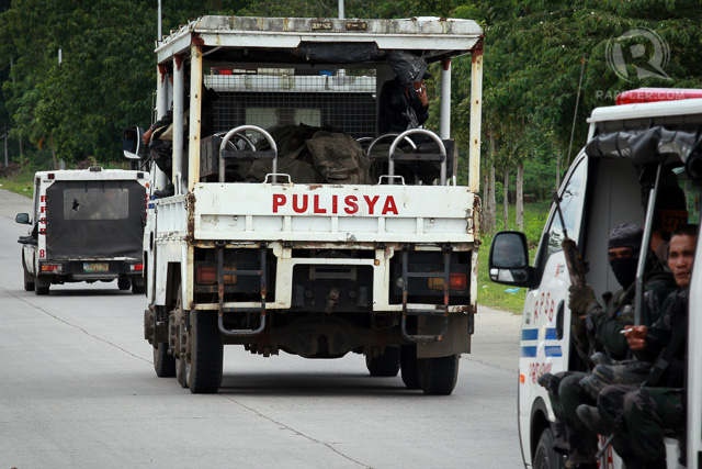 A police truck carrying the bodies of comrades passes the national highway during a retrieval operation on January 26, 2015 in Mamasapano, Maguindanao Province.
