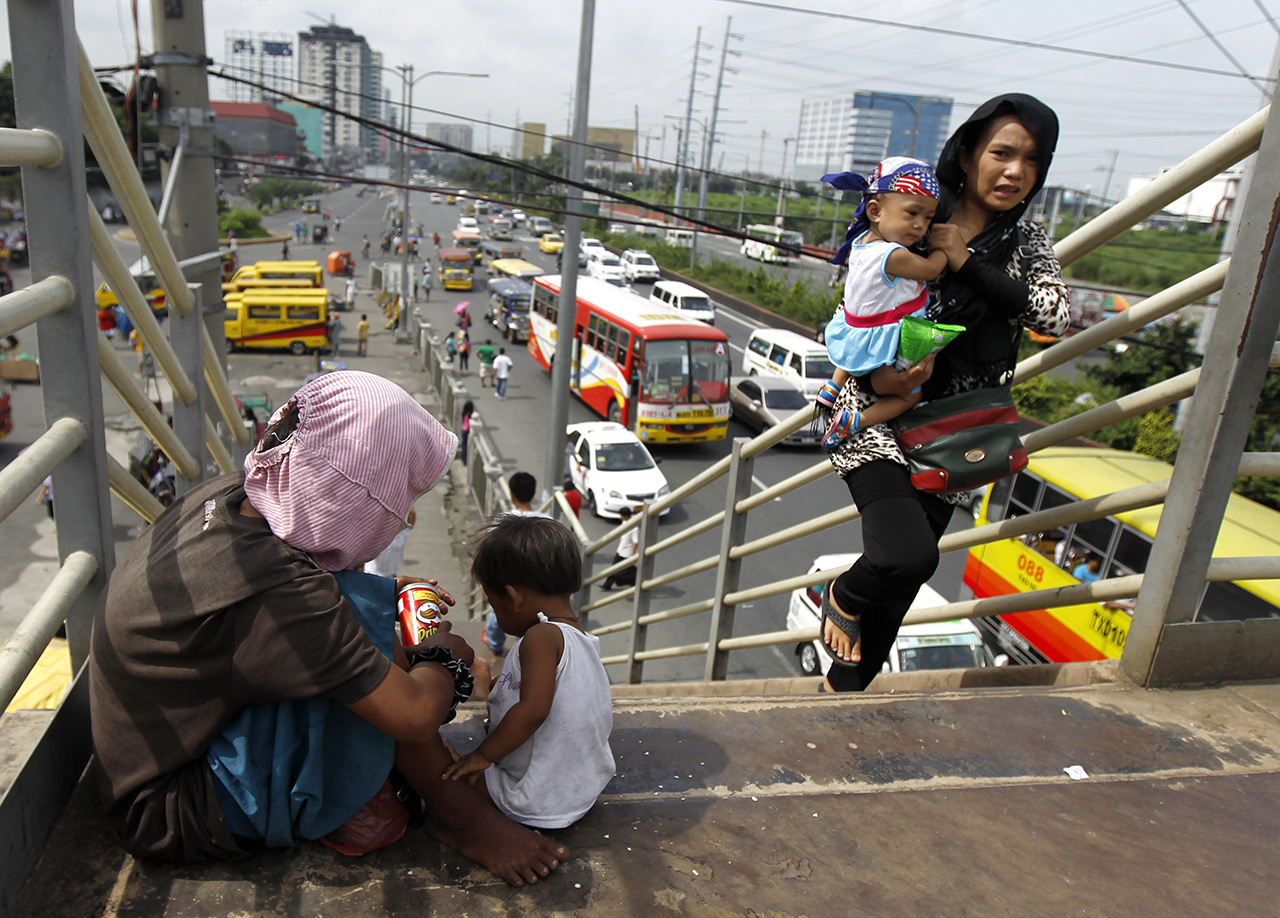 MOTHERS. A Filipino mother (L) with her baby begs for money at an elevated pathway in Paranaque City, south of Manila on August 15, 2013. File photo by Francis R. Malasig/ EPA