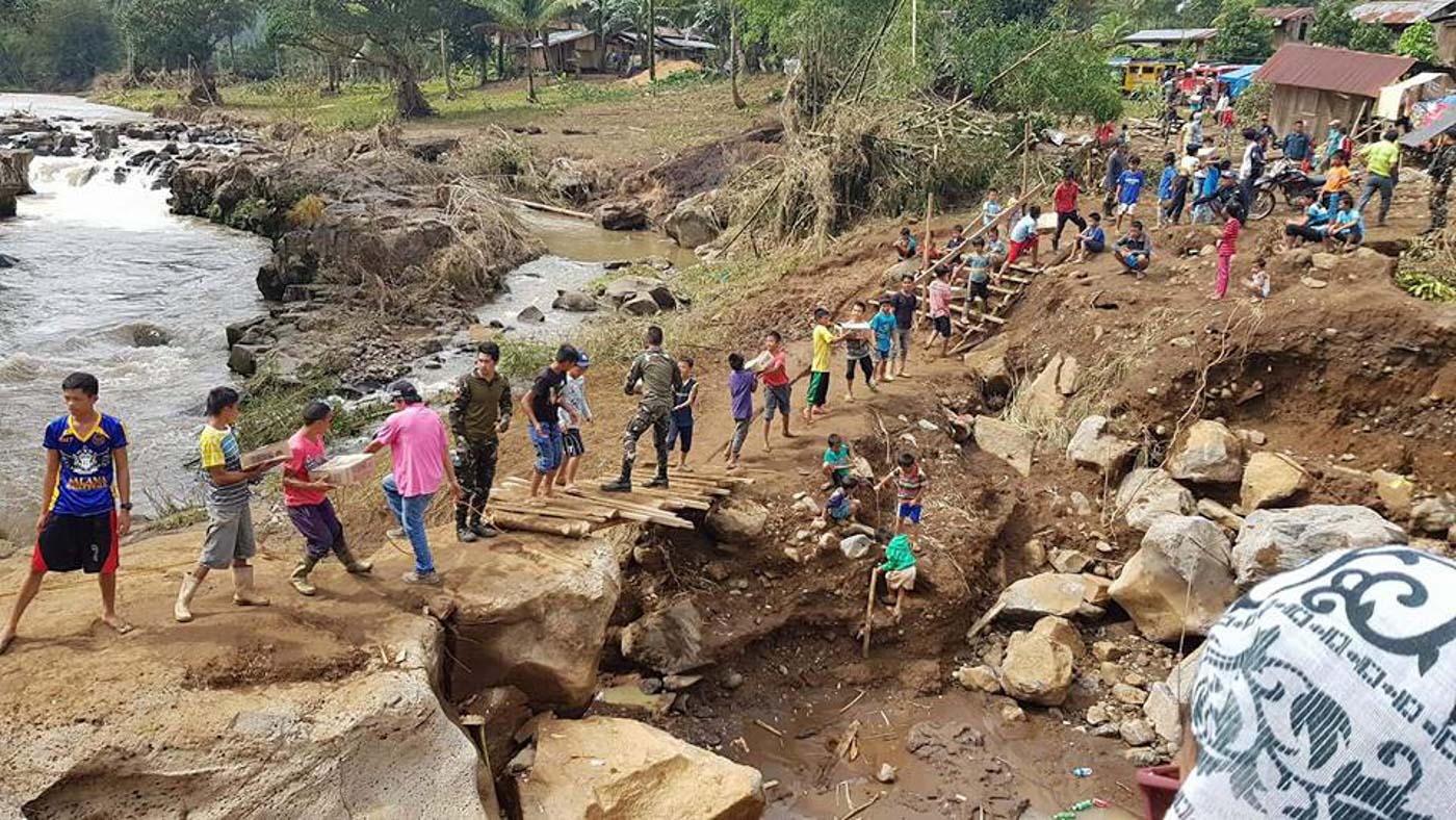 BAYANIHAN SPIRIT. Affected residents and DSWD personnel help each other in delivering relief goods to an affected village in Munai town in Lanao del Norte, which was heavily hit by Severe Topical Storm Vinta. Photo courtesy of Ninoy Castro/DSWD