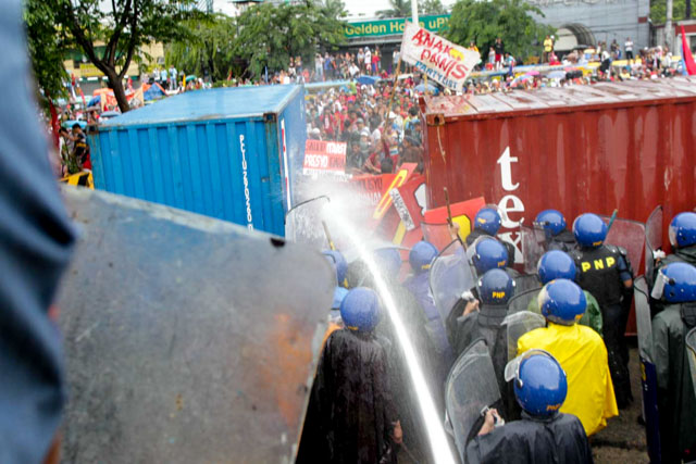 SONA RALLY. Filipino anti-riot policemen use water cannons to disperse protestors attempting to reach the Philippine Congress in Quezon City on July 27, 2015. File photo by Czeasar Dancel/Rappler