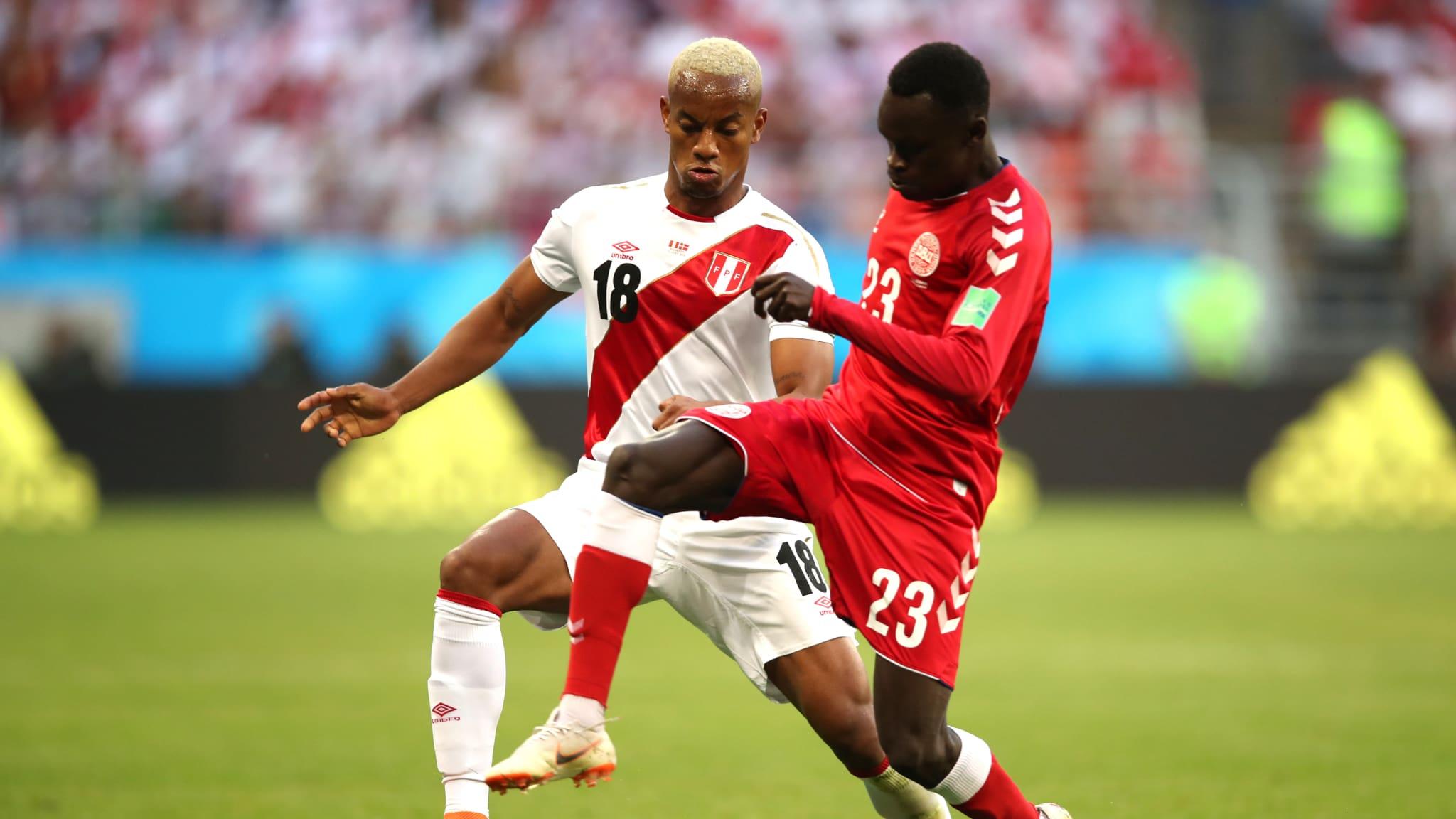 BERTARUNG. Andre Carrillo (Peru) dan Pione Sisto (Denmark) bertarung memperebutkan bola di Mordovia Arena, 16 Juni. Foto dari FIFA.com