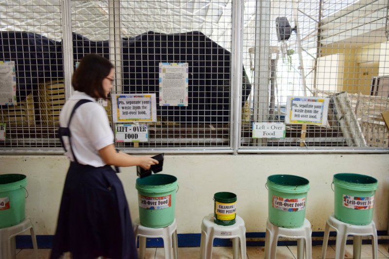 YOUTH INVOLVEMENT. A student from St. Scholastica's College in the City of San Fernando, Pampanga, places leftover food in a food bin at the school cafeteria. Photo by Khate Nolasco
