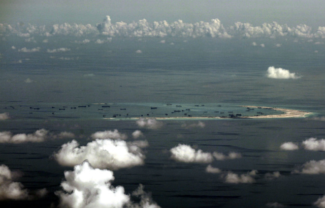 RECLAMATION ACTIVITIES. An aerial photo taken though a glass window of a military plane shows the reclamation by China on Mischief Reef, part of the disputed Spratly Islands in the South China Sea, west of Palawan, Philippines, on May 11, 2015. File photo by Ritchie Tongo/Pool/EPA