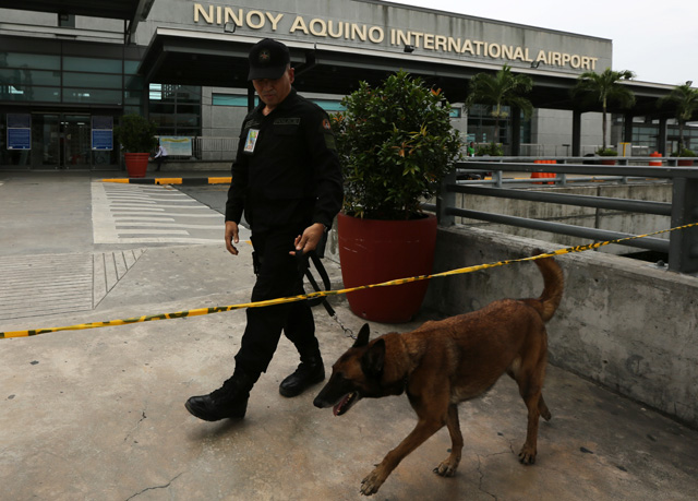 Bomb squad operatives conducts a search at the entrance of the Ninoy Aquino International Airport Terminal 3. Photo by Francis Malasig/EPA