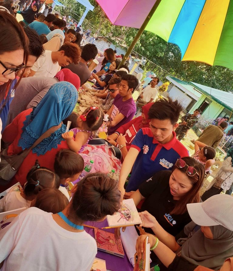 GIFT-GIVING. Movers in Isabela City, Basilan, share the table with children for distribution of Christmas gifts. Photo courtesy of Jamju Rivera