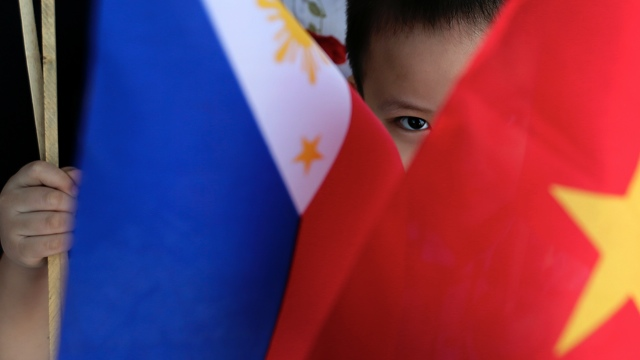 COOPERATION. A Vietnamese child peers from Vietnam and Philippines flags while waiting for the arrival of Vietnam Prime Minister Nguyen Tan Dung at Villamor Airbase in Pasay, south of Manila, Philippines, 21 May 2014. Photo by Dennis Sabangan / EPA