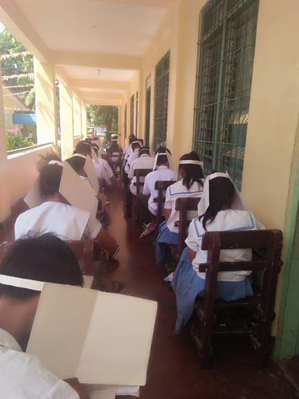 LINED. Teacher Manaug explained that since her classroom is too small for 60 students, some of the students take the exam along the hallway, still with 'anti-cheating' hats