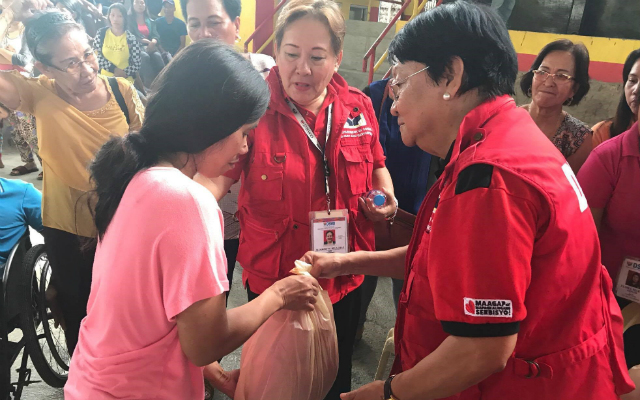 HELP NEEDED. Social Welfare Secretary Judy Taguiwalo gives relief goods to an evacuee from Marawi City. Photo from the Department of Social Welfare and Development