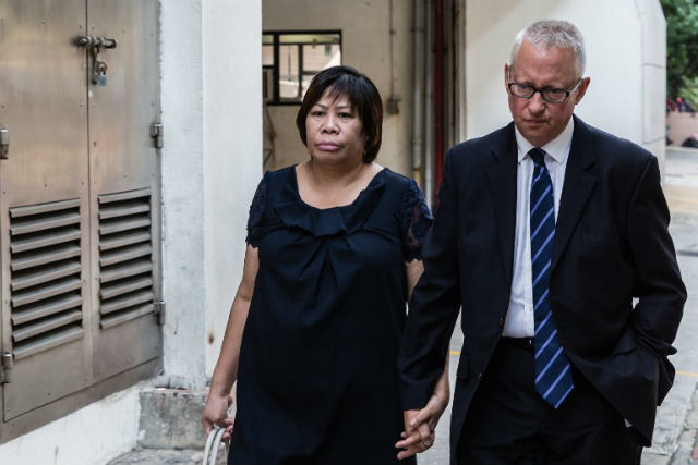 CHARGES. This photo shows Philippine national Herminia Garcia (L) and her British businessman partner Nick Cousins (R) arriving at the Eastern Magistrate Court in Hong Kong. Photo by Anthony Wallace/AFP
