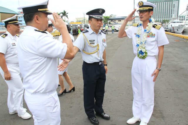 GREETINGS. Philippine and Japanese officers salute at a welcoming ceremony for the Japanese delegates. Photo by Naval Public Affairs Office.