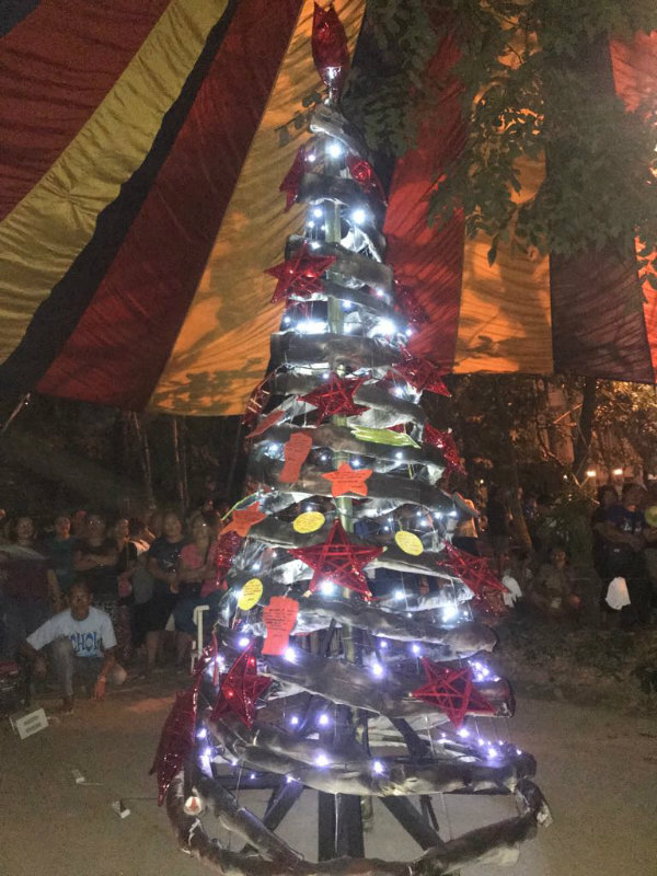 CHRISTMAS TREE. Red stars and Christmas wishes embrace the handmade branches of the tree painted in black to convey the dismay and anger of workers at the government and Sumifru.