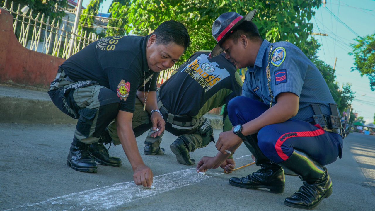 CHALK-DRAWN. The Cagayan Philippine National Police - Highway Patrol Group draws pedestrian lanes using chalk in front of Tuguegarao East Central School. Photo by Vee Salazar/Rappler