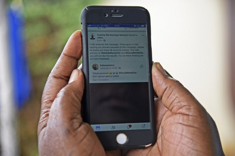 SOCIAL MEDIA TAX. A woman reads a message on social media tax as she scrolls through her Facebook account on her phone in Kampala on July 5, 2018. File photo by Isaac Kasamani/AFP