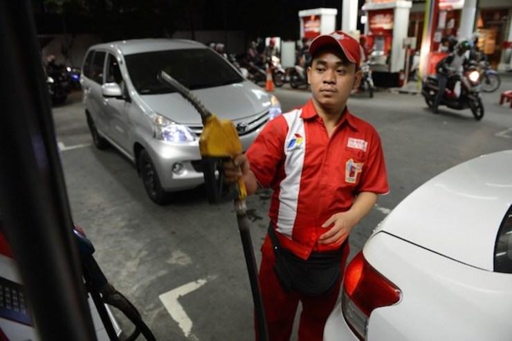 BBM NAIK. Seorang petugas SPBU mengisi BBM untuk kendaraan beberapa jam sebelum pemerintah menaikkan harga BBM bersubsidi pada Selasa, 18 November 2014, dini hari. Foto oleh Romeo Gacad/AFP