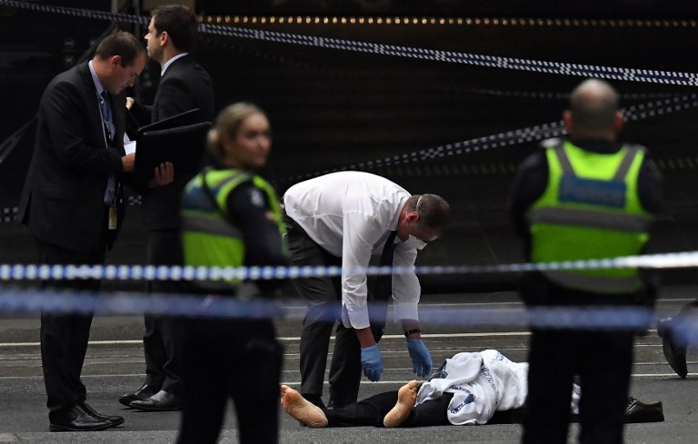 STABBING. A police officer inspects a body at the crime scene following a stabbing incident in Melbourne on November 9, 2018. Photo by  William West/AFP