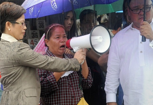 PROTEST. The mother of murder victim Jennifer Laude, Julita Cabillan (C), flanked by lawyers Virgie Suarez (L) and Harry Roque (R), uses a bullhorn as she joins protesters outside the Hall of Justice in the Philippine city of Olongapo on August 10, 2015, where the hearing for US Marine Private First Class Joseph Scott Pemberton, accused of murdering transgender Filipina Laude, was supposed to take place. Photo by Jay Directo / AFP