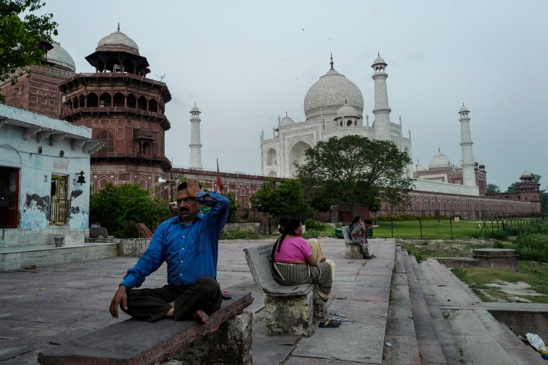TAJ MAHAL. An Indian man (left) performs yoga at the back of the Taj Mahal on the banks of the Yamuna river in Agra.  Photo by CHhandan Khanna/AFP